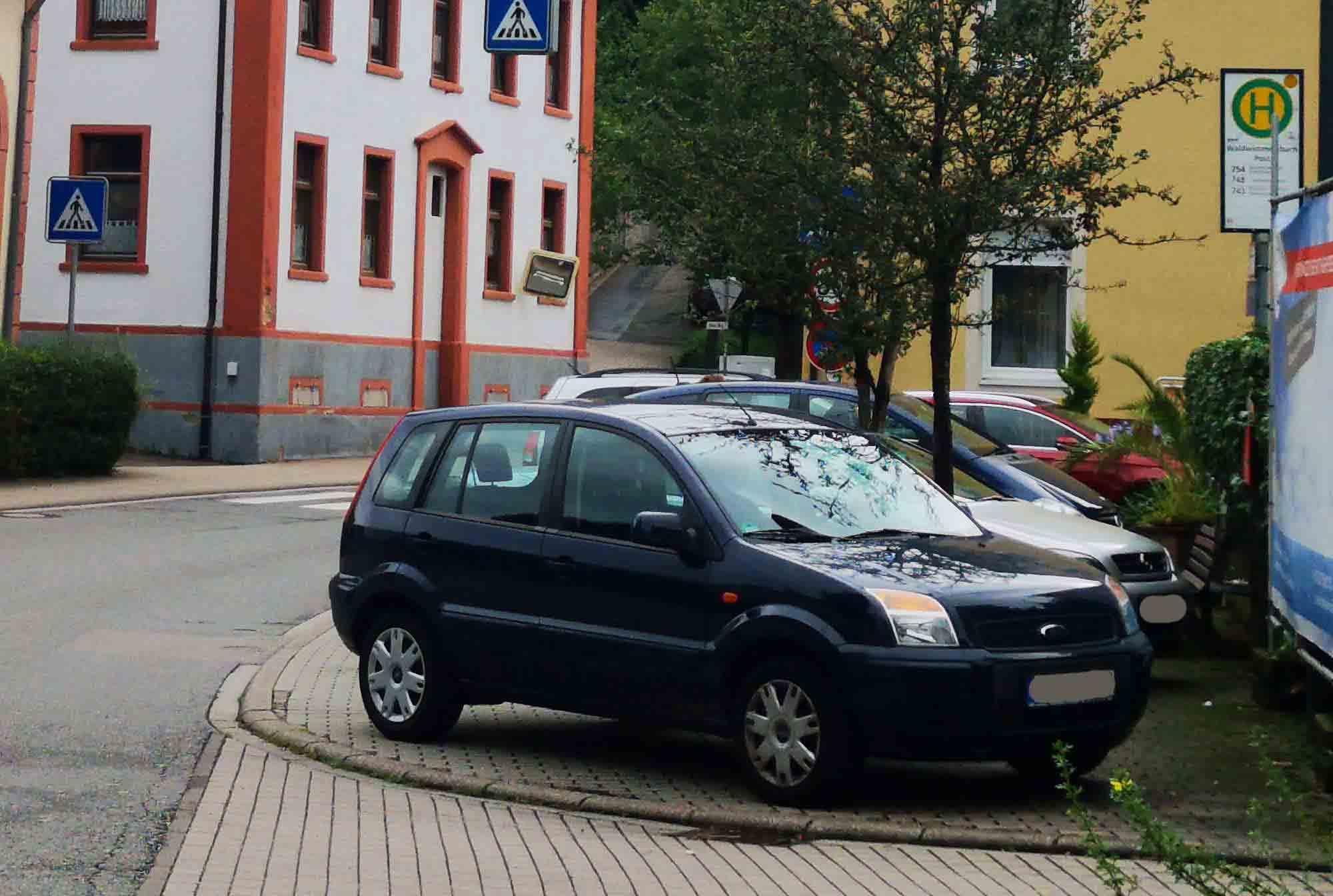 durch parkende Autos versperrt: Gehweg, Bushaltestelle und Fußgängerüberweg